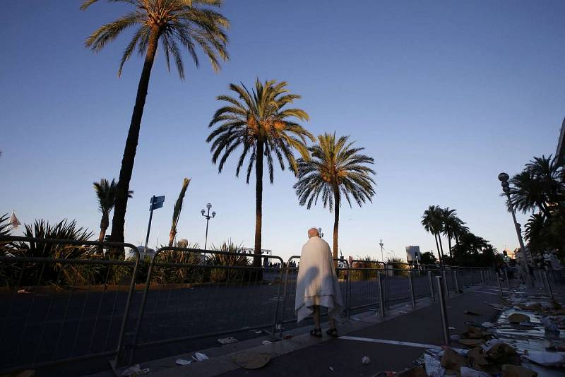A man walks through debris on the street the day after a truck ran into a crowd at high speed killing scores celebrating the Bastille Day July 14 national holiday on the Promenade des Anglais in Nice