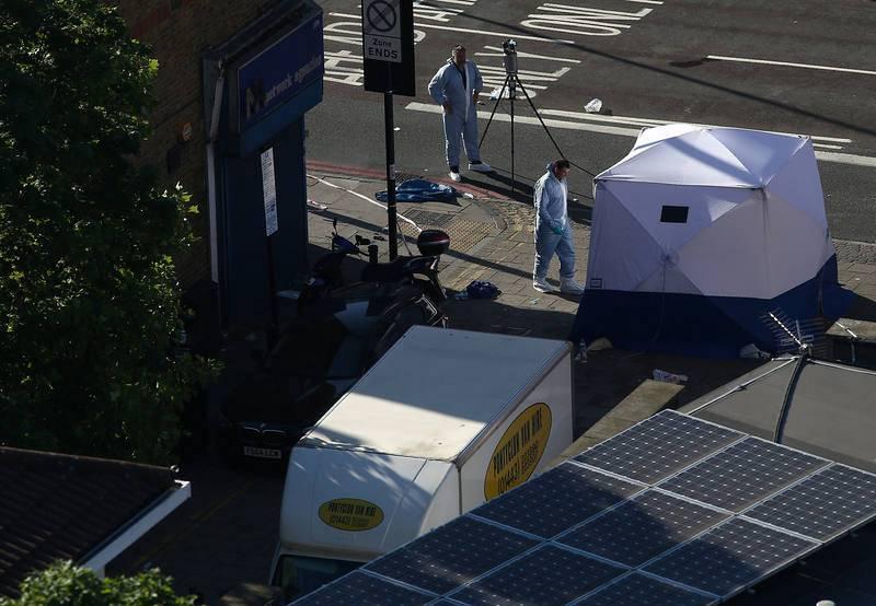 """La Policía examina la furgoneta (a la izquierda, con un logotipo amarillo) con la que un nombre ha atropellado a numerosas personas en el norte de Londres. La Policía asegura que el suceso tiene todas las características de un """"atentado terrorista""""."""