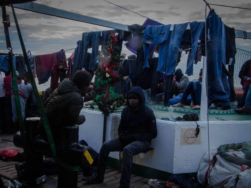 Ropas tendidas en la proa del OPEN ARMS donde algunos de los rescatados descansan junto al improvisado árbol de Navidad que han montado los voluntarios