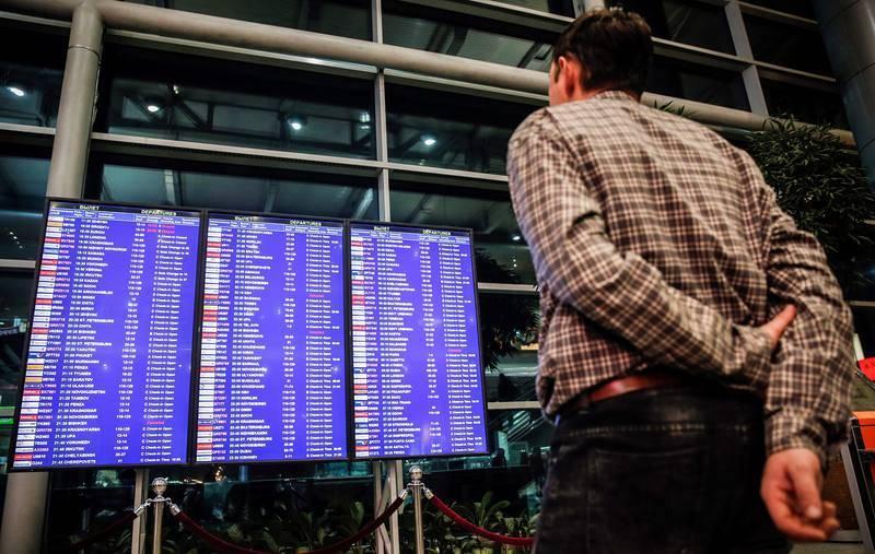 Un hombre mira un panel de vuelos en el aeropuerto Domodédovo de Moscú