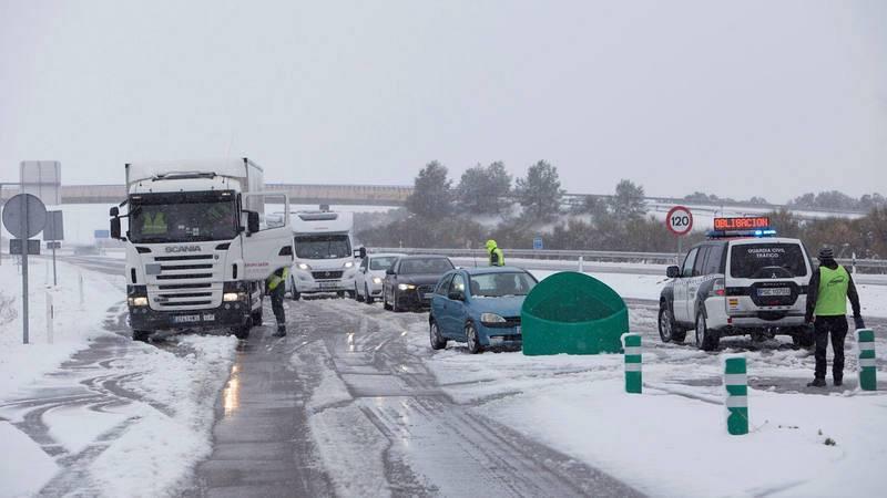 Una patrulla de Tráfico de la Guardia Civil en la autopista A-23, en Huesca, informa a los conductores del uso obligatorio de cadenas