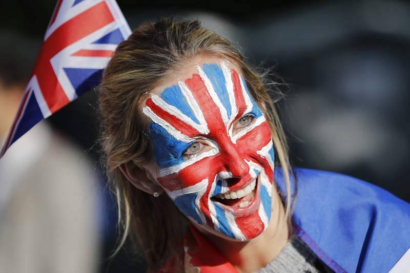 Una mujer espera a los novios con la cara pintada con la bandera de Reino Unido