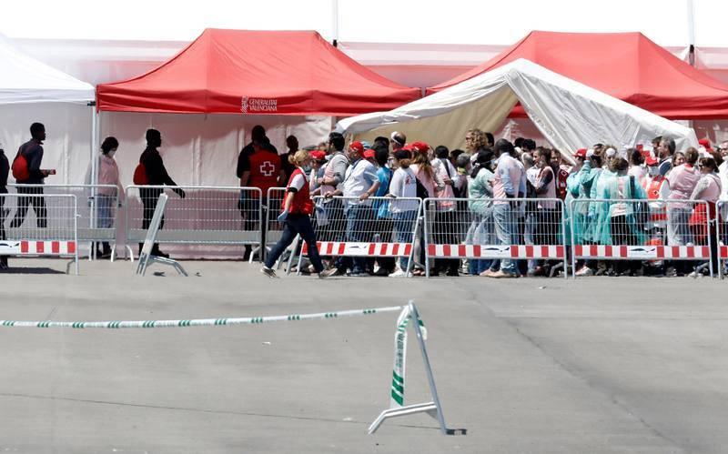 Varios de los 106 inmigrantes que viajaban en el Aquarius, esperan ser atendidos tras la llegada del buque al puerto de Valencia
