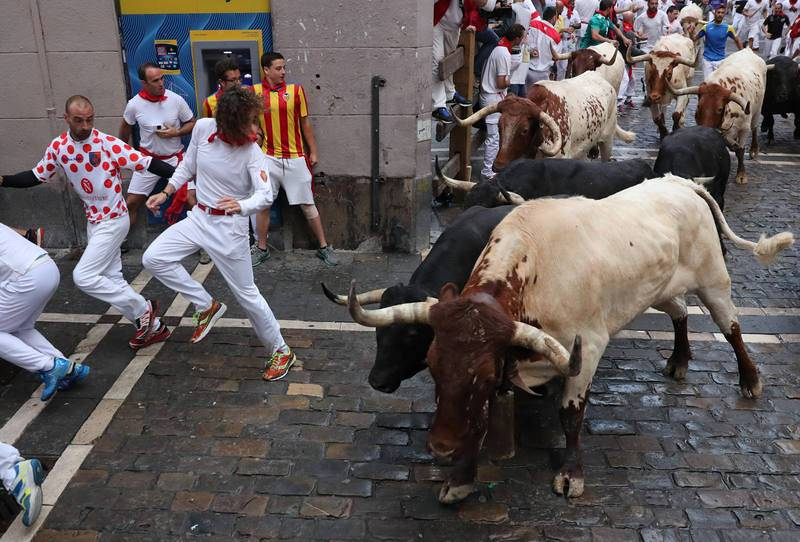 Revellers sprint in front of bulls during the sixth running of the bulls of the San Fermin festival in Pamplona