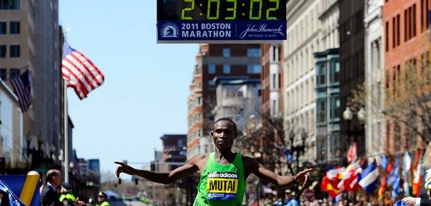 Momento en que Mutai cruza la meta de Boston con su récord reflejado en la parte superior