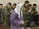 A resident and South Korean marines pray during a Christmas mass at a Catholic church on Yeonpyeong island