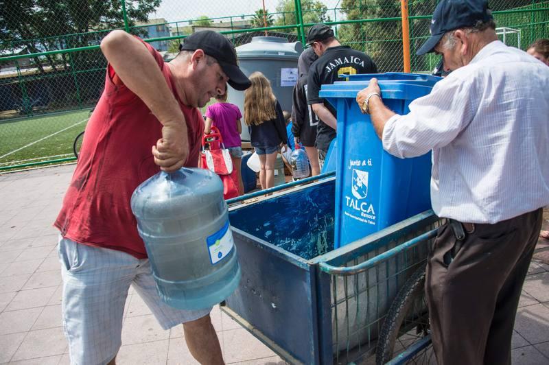 Afectados por los cortes de agua acuden a uno de los puntos de suministro habilitado por las autoridades.