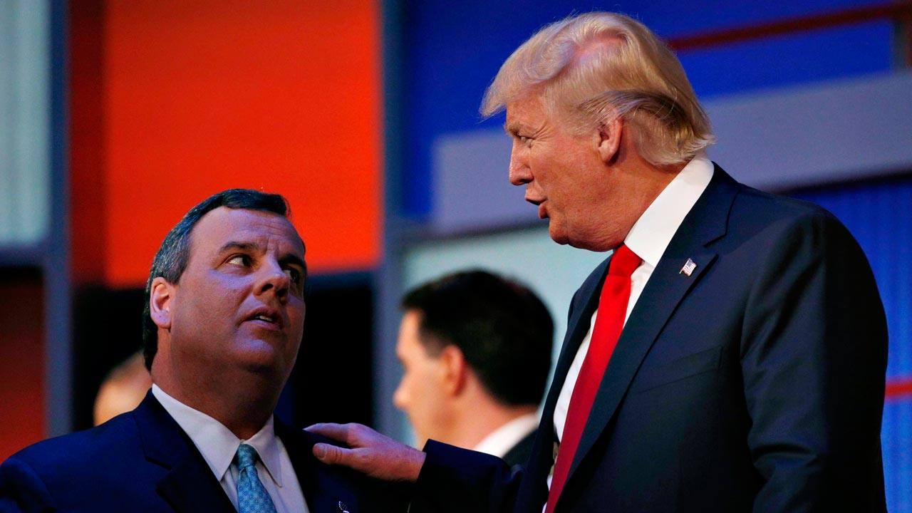 Chris Christie, a la izquierda, charla con Donald Trump durante la publicidad en un debate televisado del 6 de febrero