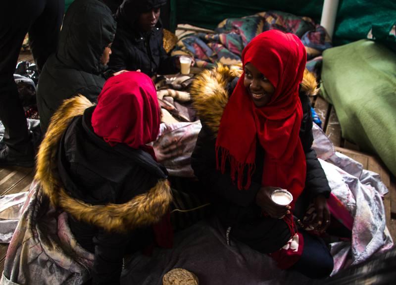 Dos chicas charlan en la cubierta del OPEN ARMS mientras toman la leche caliente enriquecida que les acaban de dar.