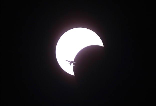 Un avión atraviesa el cielo durante el eclipse anular más largo del milenio, que se pudo ver en Asia en África.