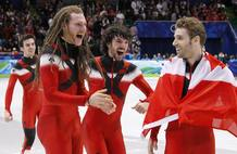 Members of the Canadian team celebrate after winning the gold medal in the men's 5000 metres relay short track final at the Vancouver 2010 Winter Olympics