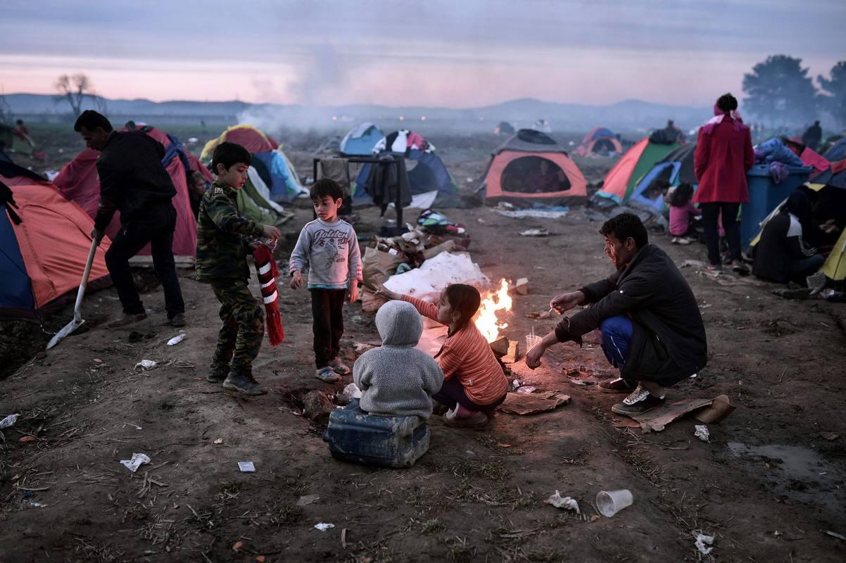 Una familia intenta calentarse en torno a un fuego en el campamento de Idomeni, en la frontera entre Grecia y Macedonia