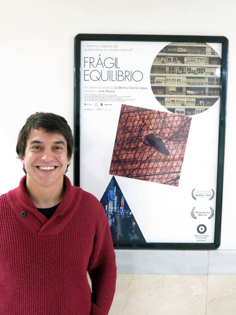 Guillermo García, director de 'Frágil Equilibrio', junto al cartel de su película en los Cines Renoir de Madrid.