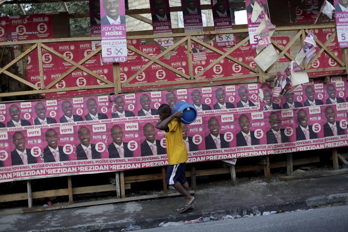 Un hombre pasa en Puerto Príncipe ante una pared forrada de carteles del candidato oficialista, Jovenel Moise