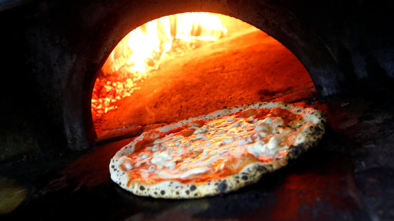 Pizza Margherita is prepared in a wood-fired oven at L'Antica Pizzeria da Michele in Naples