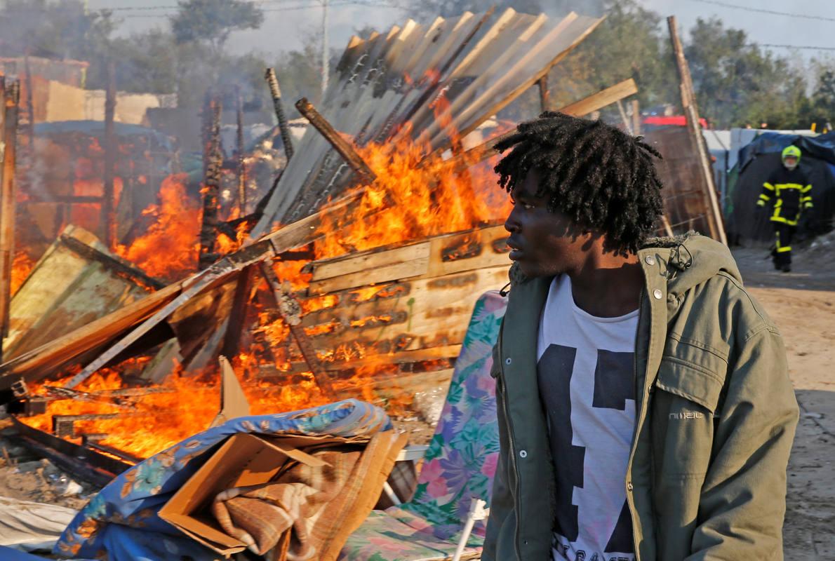 Un inmigrante pasa junto a la chabola que ha ardido en el 'jungla de Calais'