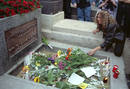 A woman puts flowers on the grave of lead singer of US rock group the Doors Jim Morrison on the 25th..