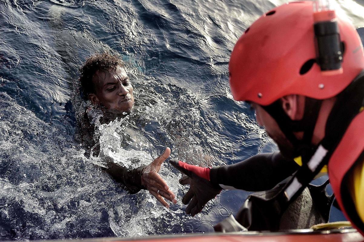 Un miembro de la ONG Proactiva Open Arms ayuda a sacar del agua a un migrante