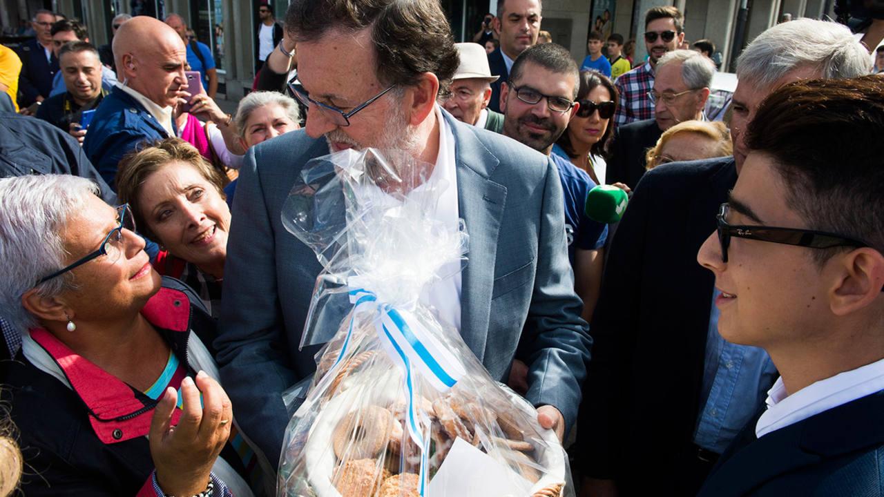 Una simpatizante regala una bolsa de rosquillas a Mariano Rajoy durante un paseo electoral en Pontedeume (A Coruña)