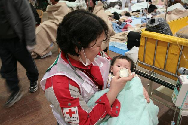 A member of the Japanese Red Cross feeds a baby, a survivor of an 8.9-magnitude earthquake and tsunami, at Ishinomaki Red Cross hospital in Miyagi prefecture