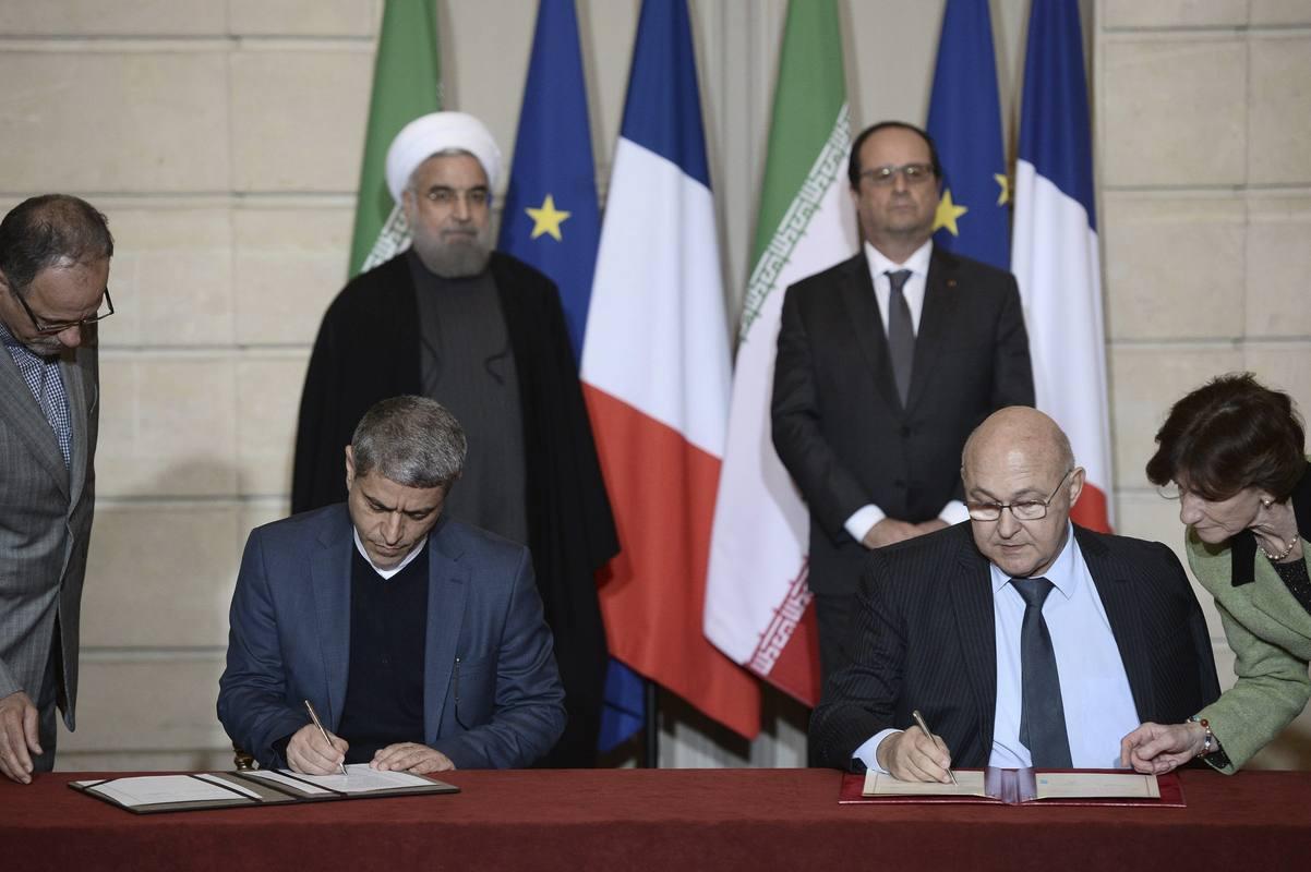 El ministro francés de Finanzas, Michel Sapin (a la derecha) y su homólogo iraní, Alí Tayebnia (a la izquierda), firman algunos de los acuerdos bilaterales en presencia del presidente iraní, Hasán Rohaní, y el presidente francés, François Hollande