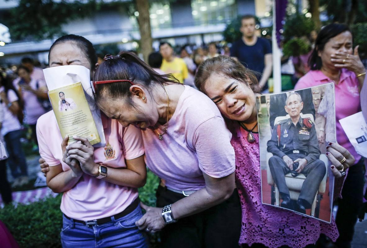 Dos mujeres tailandesas lloran tras conocer el fallecimiento del rey Bhumibol Adulyadej en Bangkok.