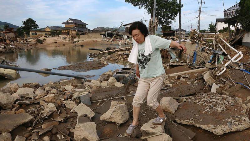 Una mujer camina por los escombros ocasionados por las inundaciones en la ciudad japonesa de Kurashiki.