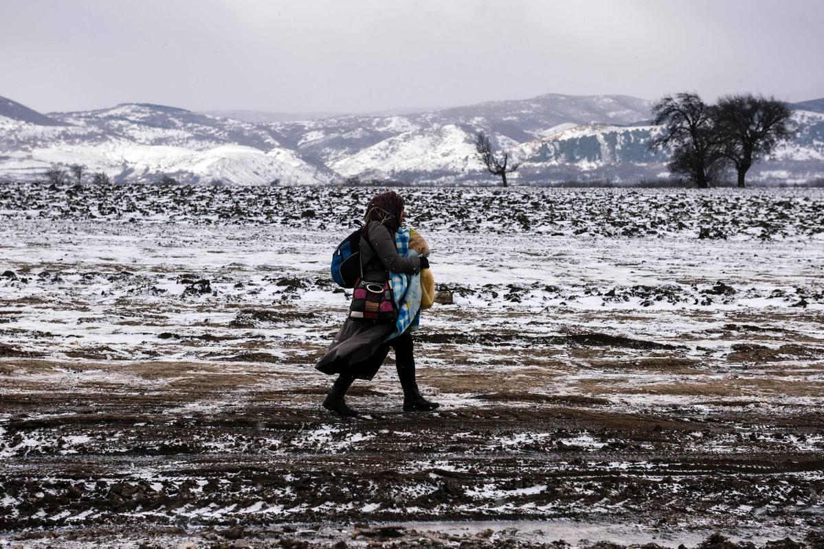 Una mujer refugiada cruza en mitad de la nieve la frontera entre Macedonia y Serbia.