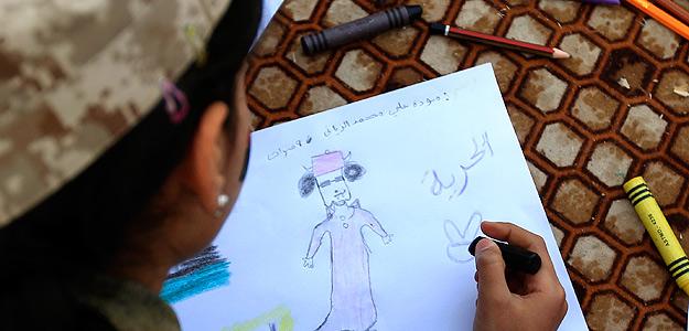 "Una niña libia dibuja una caricatura de Gadafi junto con la palabra ""Libertad"", en Bengazi"
