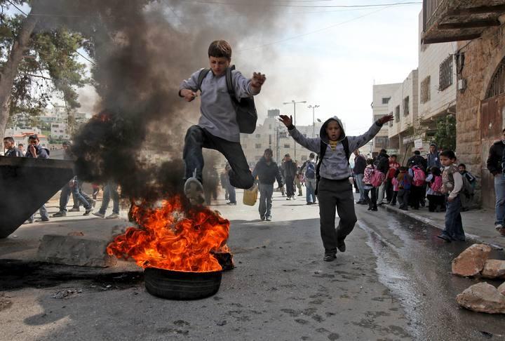 Un niño palestino salta sobre un neumático en llamas durante una nueva jornada de enfrentamientos en la ciudad cisjordana de Hebrón.
