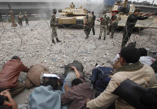 Opposition supporters lay down on the ground in front of Egyptian army tanks on the frontline near Tahrir Square in Cairo