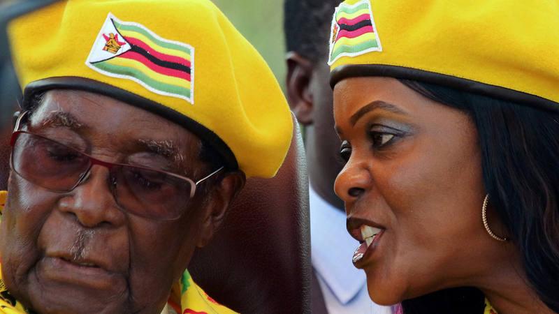 El presidente de Zimbabue, Robert Mugabe, escucha a su mujer, Grace, en un mitin del partido ZANU-PF