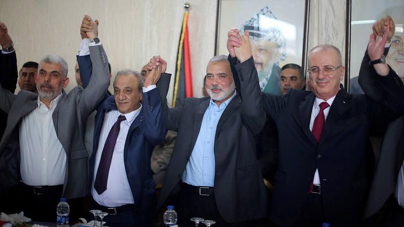 El primer ministro palestino, Rami Hamdallah (derecha) y el líder de Hamás, Ismail Haniyeh (segundo por la derecha), estrechan sus manos durante la visita del primero a Gaza el 2 de octubre.