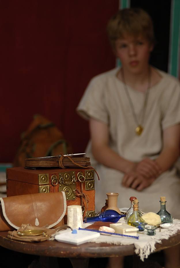 Redomas con perfumes y otros objetos de lujo. El niño lleva la bulla, una bolsa, con amuletos protectores, colgada del cuello