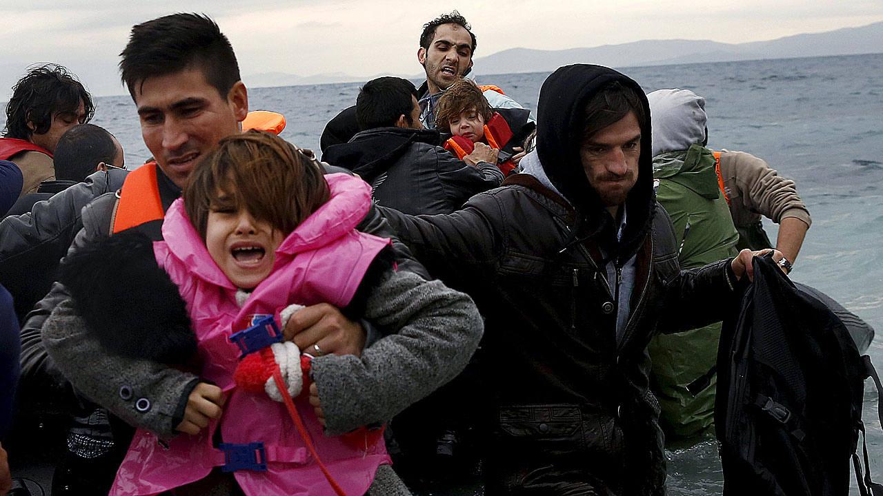 Refugiados y migrantes llegan en una balsa inflable a la isla griega de Lesbos.