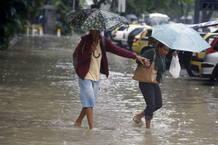 Dos mujeres se protegen de la lluvia en medio de las inundaciones en Río.