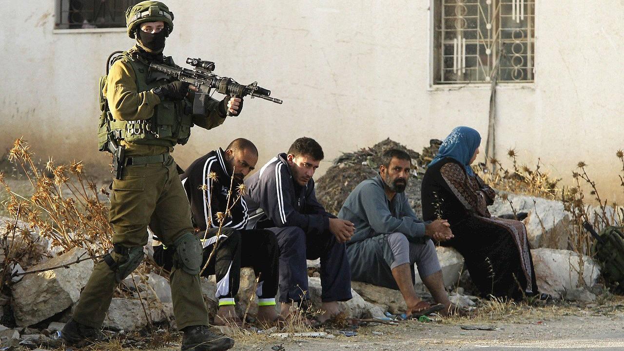 Un soldado israelí vigila a un grupo de palestinos en la aldea de Yatta, cerca de Hebrón, en Cisjordania