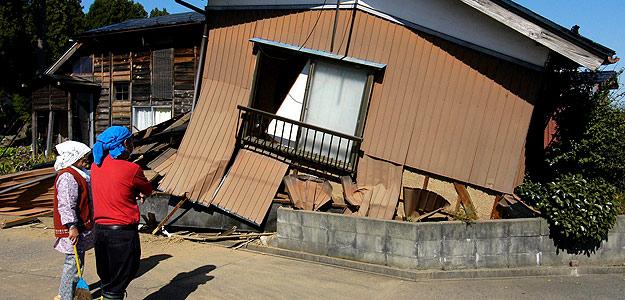 Fotografía de archivo tomada el 24 de octubre de 2004 que muestra a una mujer y su vecino observando su casa derruida tras un terremoto de 6,8 grados de magnitud el día anterior en Ojiya al noroeste de Tokio en Japón
