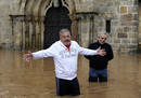 Two men stand on a flooded street in Villaviciosa
