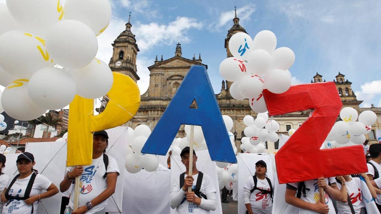 Varios asistentes a la ceremonia sostienen las letras que conforman la palabra PAZ