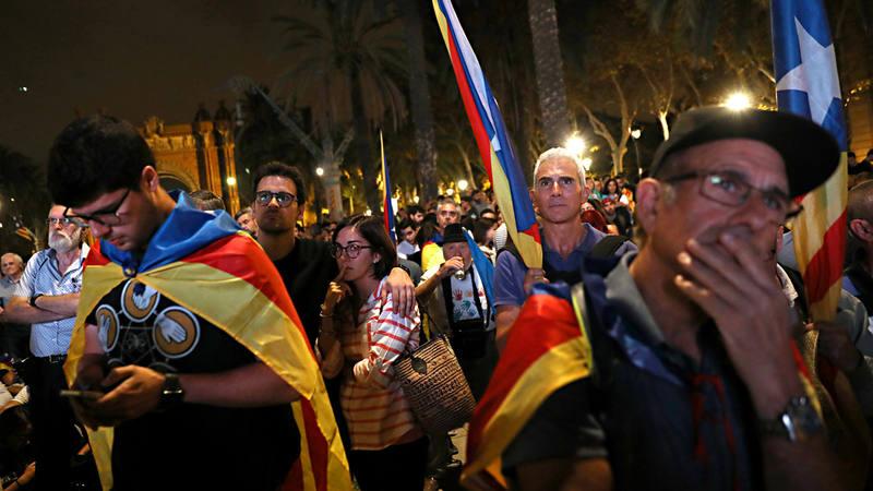 Varios de los independentistas congregados junto al Parlament siguen la declaración del Puigdemont