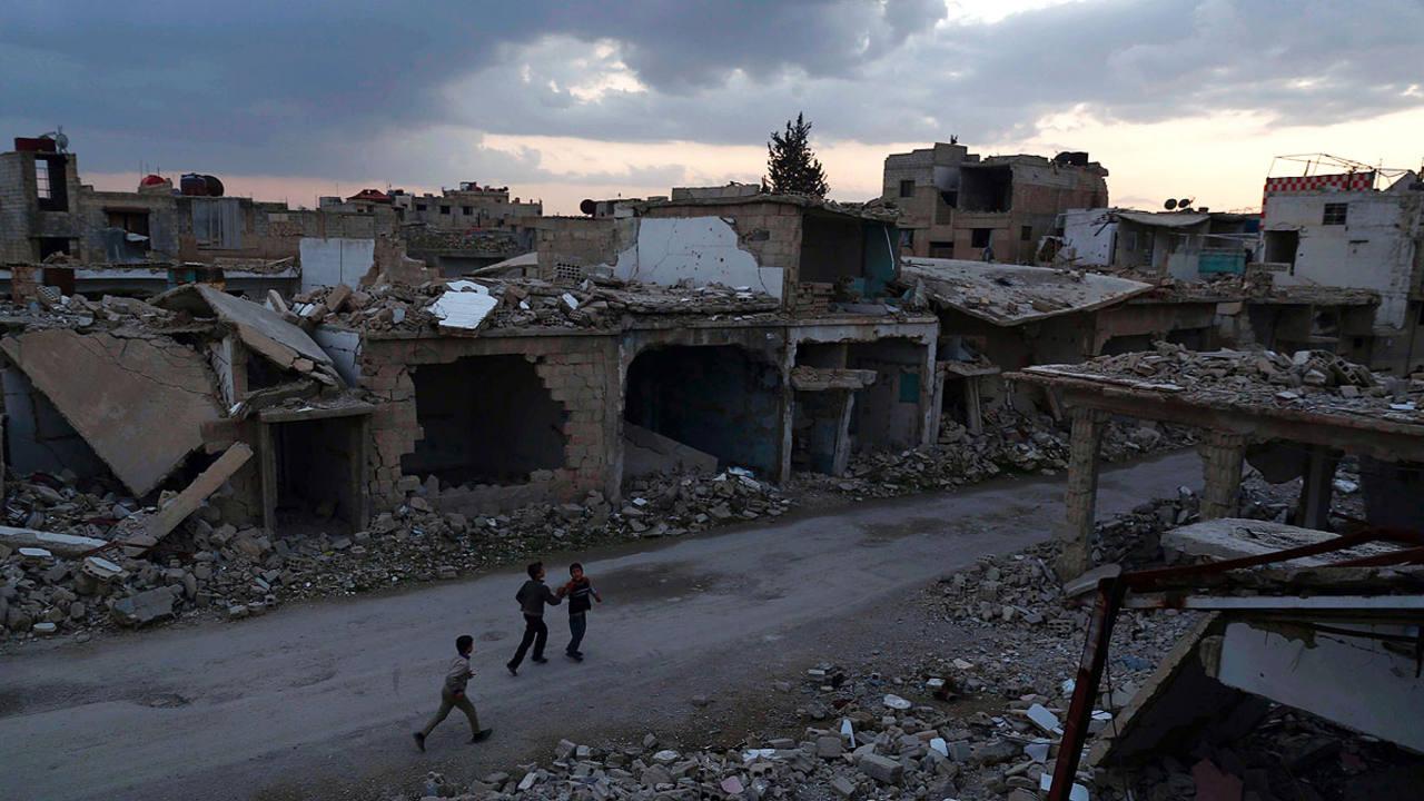Varios niños corren por la ciudad Siria de Duma, destruida por la guerra