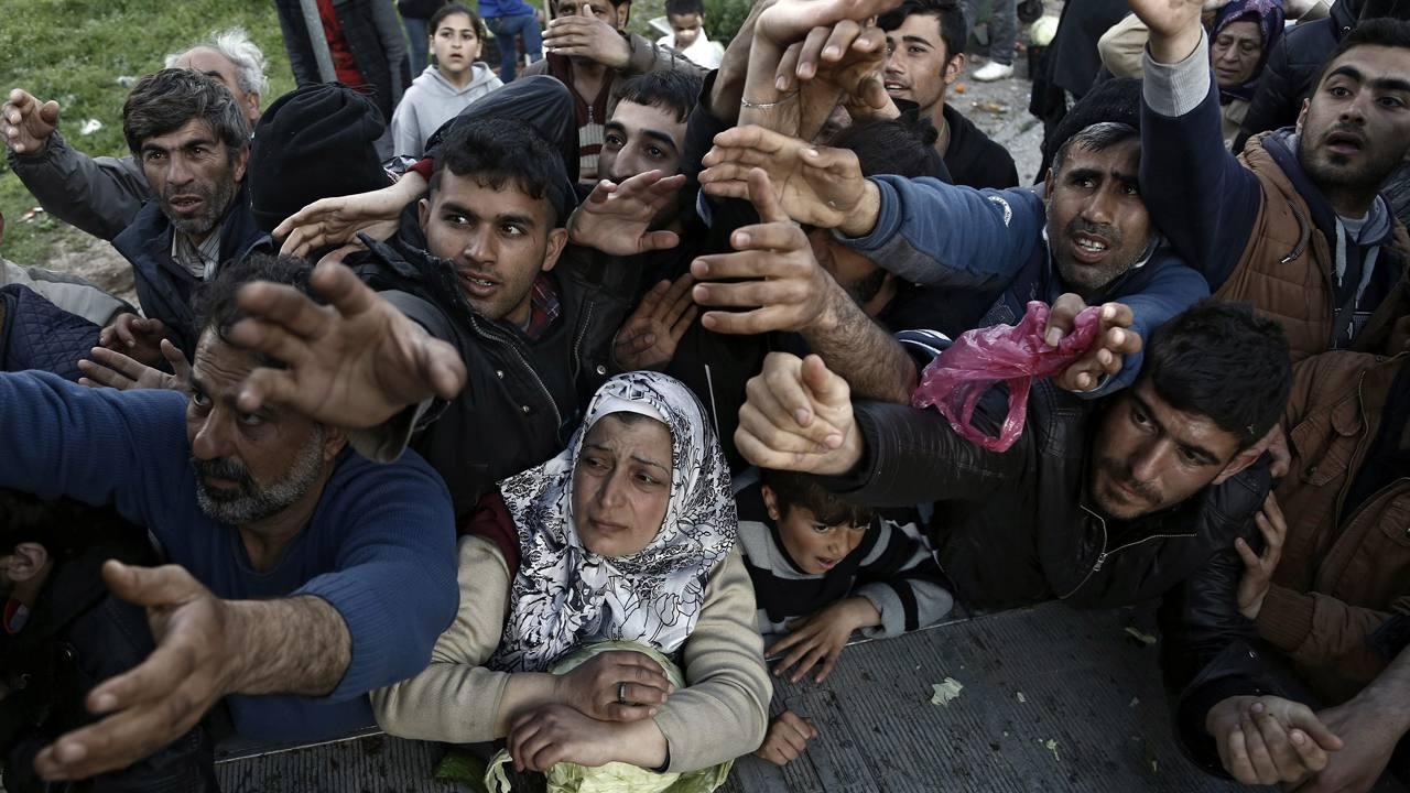 Varios refugiados pelean por comida cerca de la localidad de Idomeni, en la frontera entre Grecia y Macedonia