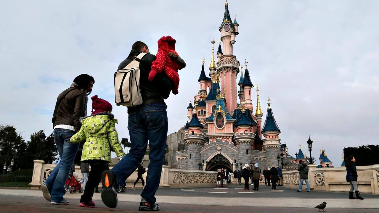 Varios visitantes del parque temático Disneyland París, junto al castillo de la Bella Durmiente