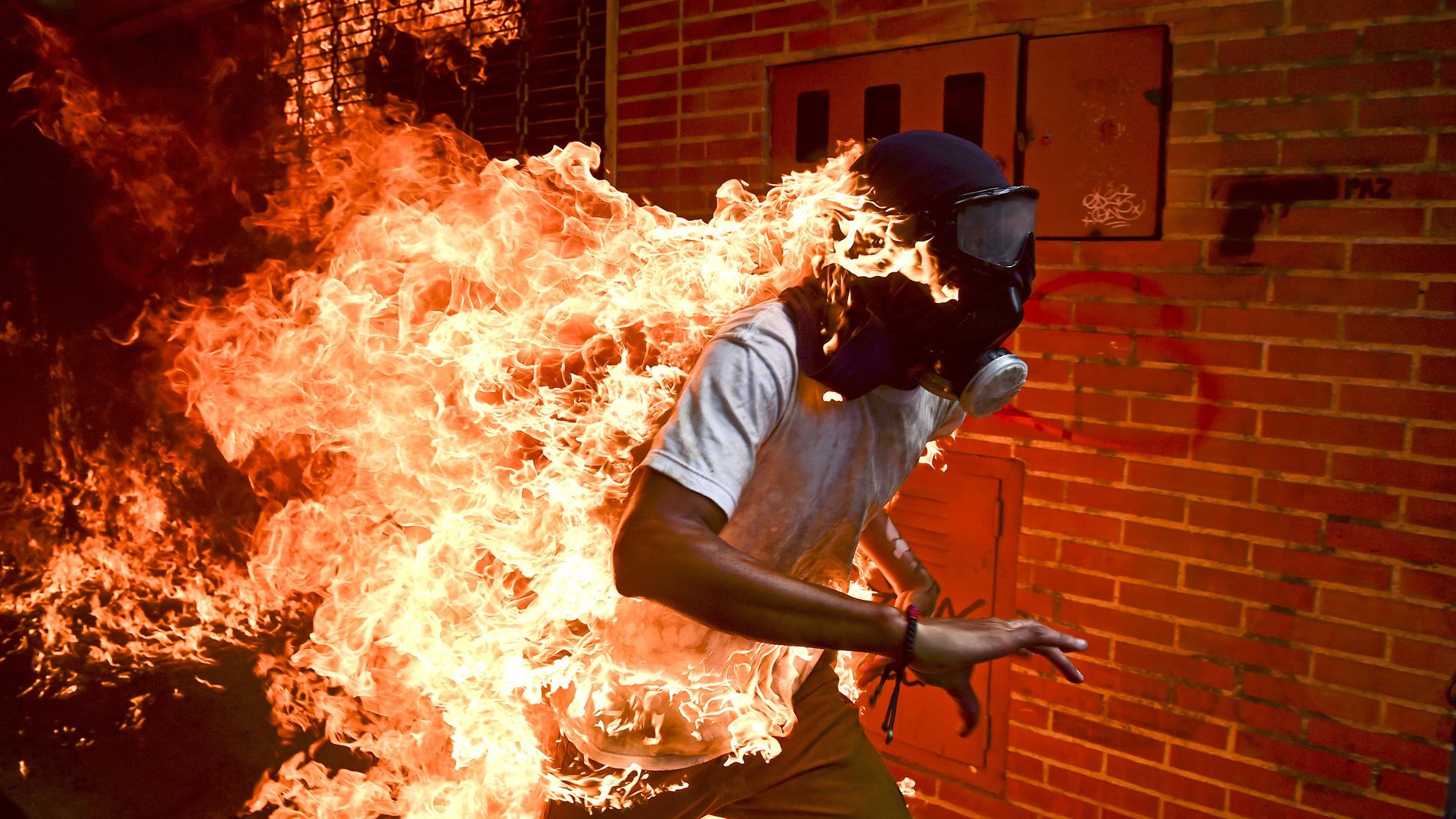 El venezolano Ronaldo Schemidt recibe el World Press Photo por una imagen de unos disturbios en Caracas