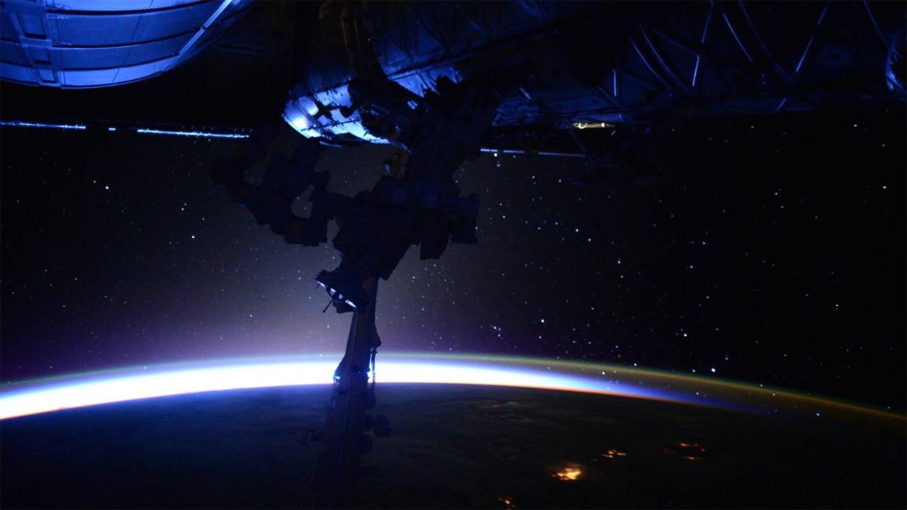 Vista parcial de la estructura de la Estación Espacial Internacional, iluminada por el reflejo de la Tierra. (SCOTT KELLY)