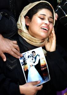 Una mujer palestina llora y muestra la fotografía de la boda con su marido ya fallecido.