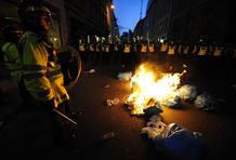 La policía protege el fuego ocasionado por algunos manifestantes.