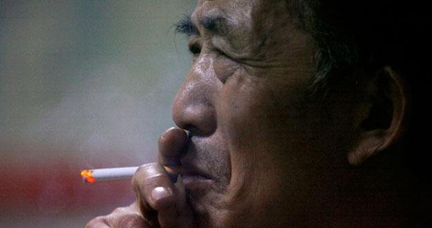 Un anciano fuma un cigarrillo en un mercado de Nanjing.