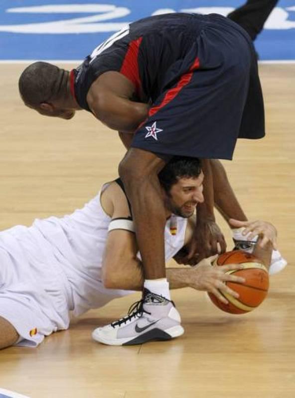 El jugador Alex Mumbru (en el suelo) lucha por el balón con el estadounidense Kobe Bryant.
